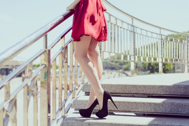 Side view photo portrait of sexual seductive fit slim long legs, red retro shiny colorful chiffon elegant dress. happy girl waiting lover walking in city center, relaxing. blurred background concept