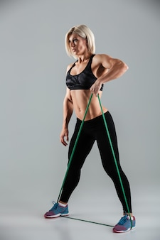 Side view photo of sports woman exercising with resistance band