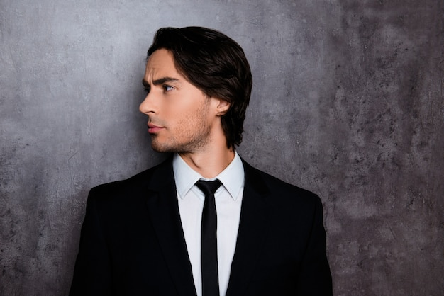 Side-view photo of stylish young man in formalwear with stubble