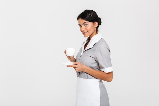 Side view photo of tidy maid in gray uniform holding cup of coffee while standing and looking aside