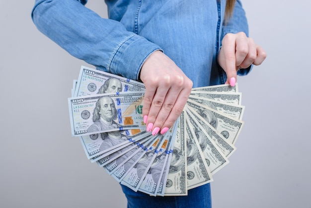 Side view photo of woman holding pile of money