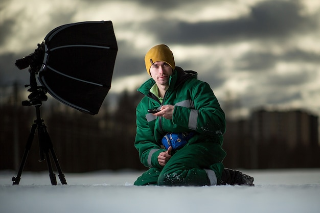 Side view at the photographer sitting on snow at winter field takes autoportrait