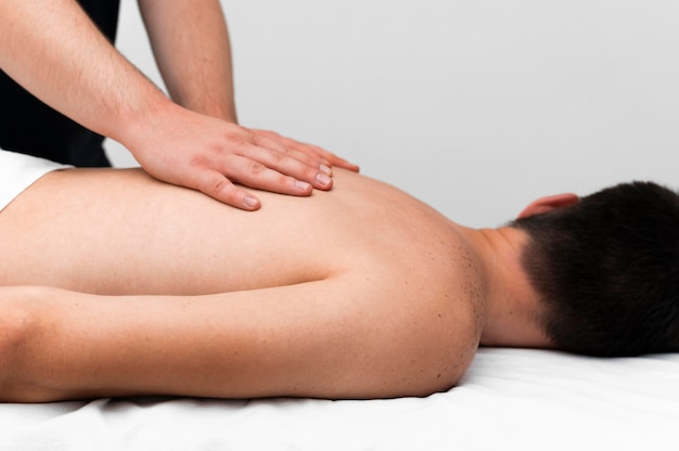 Side view of physiotherapist massaging man's back