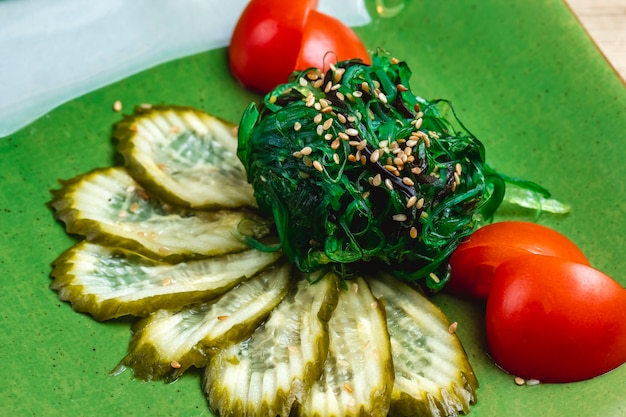 Vista laterale marinato cetrioli alghe e pomodoro sul tavolo