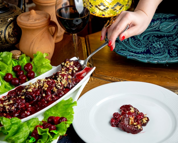 Side view of pickled fruit salad with walnuts  hand picking up food from a salad plate