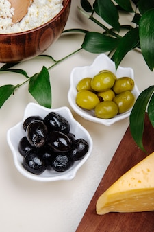 Side view of pickled olives with various kind of cheese on white table