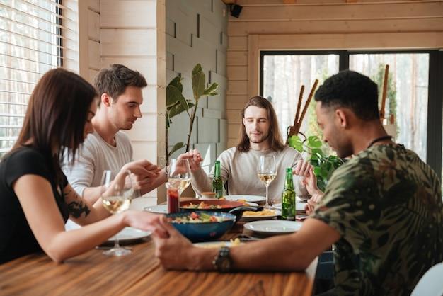 夕食のテーブルの上で祈っている友人のグループの側面図の写真