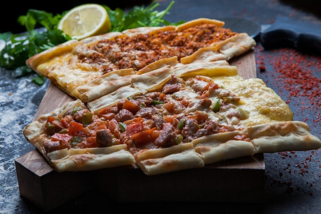 Side view pide with pieces of meat and parsley and lemon and pizza knife in cutting board