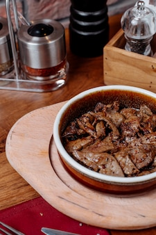 Side view of pieces of beef fried in a clay bowl with spices on a wooden board