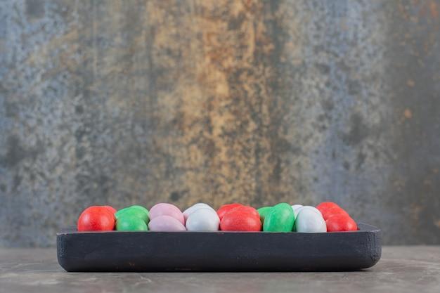Vista laterale del mucchio di caramelle dolci colorate sul piatto di legno.