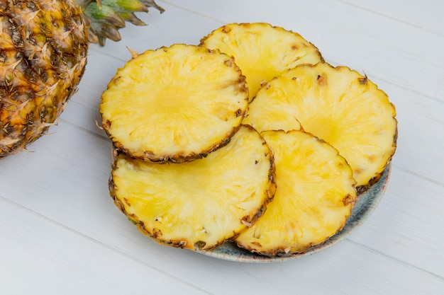 Side view of pineapple slices in plate with whole one on wooden background