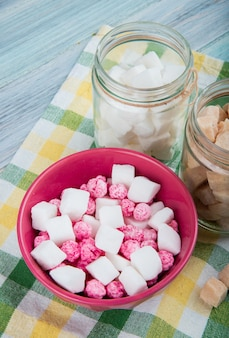 Side view of pink sugar candies in a bowl and different types of sugar in glass jars on plaid table napkin on rustic background