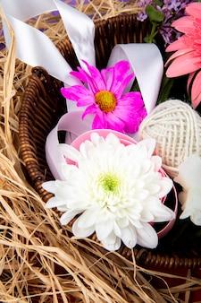 Vista laterale di fiori di crisantemo di colore rosa e bianco con gerbera e fiori lilla in un cesto di vimini con paglia su sfondo viola