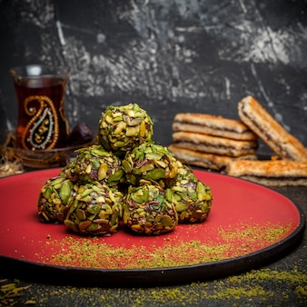 Side view pistachio cookies on red round platform with cookies and tea on dark textured background.