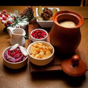 Вид сбоку пити с крекерами и зернами граната и солеными огурцами в глиняном кувшине на деревянном столе