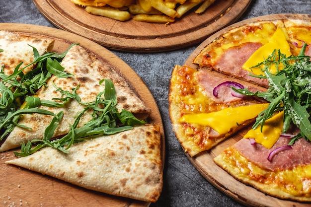 サイドビューピザハムと赤玉ねぎのチーズピザとテーブルの上のルッコラの溶けたチーズカルゾーネピザ