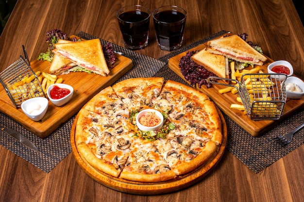 Side view of pizza with chicken and mushrooms served with sauce and vegetables salad on wooden plate