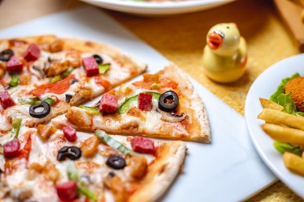 Вид сбоку пицца с жареной курицей салями болгарский перец, маслины и сыр на столе