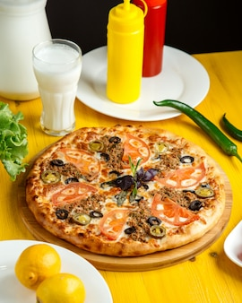 Side view of pizza with minced meat tomatoes and olives on wooden plate