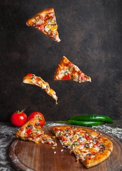 Side view pizza with pepper and tomato and pizza slices in board cookware