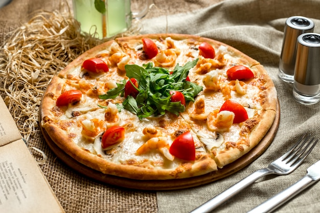 Side view pizza with shrimp and mushrooms tomatoes and arugula and with a soft drink