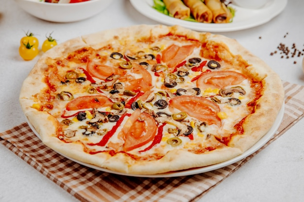 Side view of pizza with tomatoes mushrooms and olives