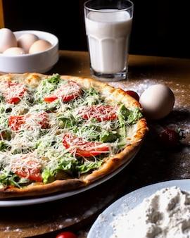 Pizza vista laterale con pomodori con uova un bicchiere di latte e farina sul tavolo