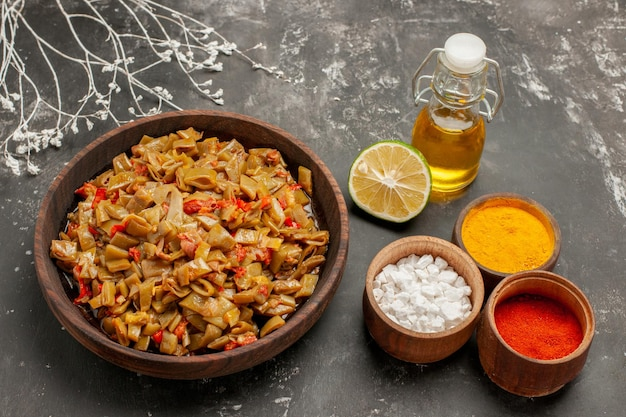 Vista laterale piatto di fagioli e spezie ciotole di tre tipi di spezie colorate il piatto di fagiolini accanto ai rami degli alberi e bottiglia di olio sul tavolo scuro
