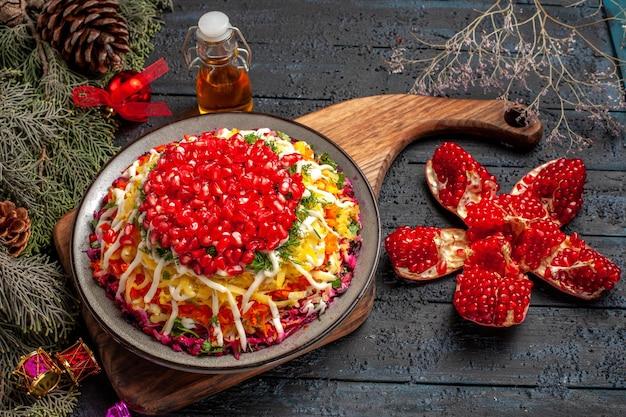 Piatto vista laterale del cibo natalizio piatto natalizio con melograno sul tagliere bottiglia di melograno in pilled di olio e rami di abete rosso con i giocattoli dell'albero di natale