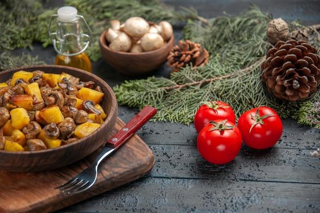 Вид сбоку тарелка с едой деревянная миска с картофелем с грибами на разделочной доске рядом с вилкой и помидорами под масляной миской с белыми грибами и еловыми ветками