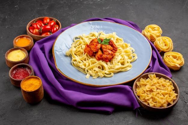 Vista laterale piatto di ciotole di pasta di pomodori quattro tipi di salse e piatto di pasta e sugo sulla tovaglia viola