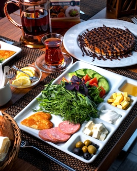 Side view of a plate with breakfast food fresh vegetable salad cheese honey fried eggs and sausages served with tea and desert
