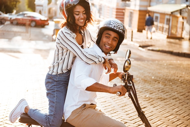 Side view of pleased african couple rides on modern motorbike on the street