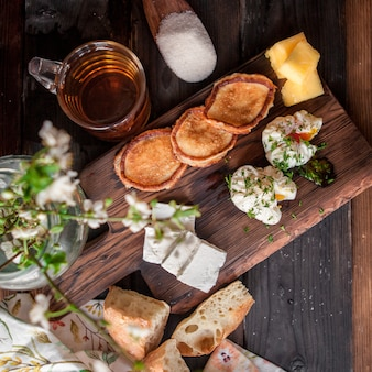 Side view poached egg with pancakes and cup of tea and bread in board cookware on wooden table