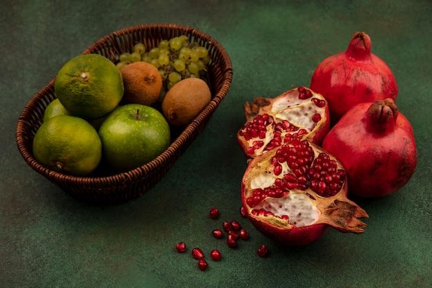 緑の壁のバスケットにみかんリンゴブドウとキウイとザクロの半分の側面図