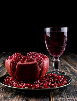 Side view pomegranate seeds with glass of juice