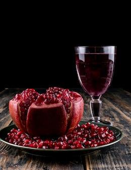 Вид сбоку семена граната со стаканом сока