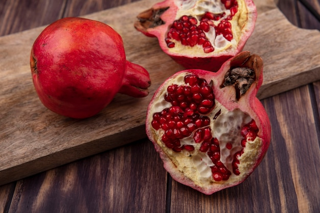 Side view pomegranates on a cutting board on a wooden wall