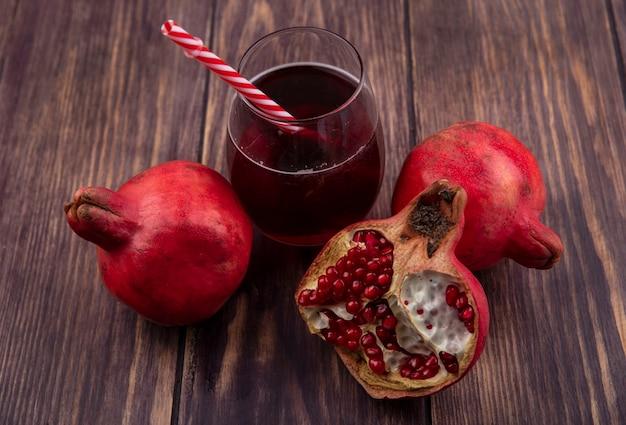 Гранаты со стаканом сока и красной соломкой на деревянной стене, вид сбоку