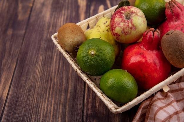Вид сбоку гранаты с мандаринами, яблоками и киви в корзине на деревянной стене