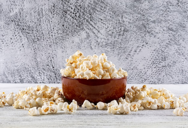 Side view of popcorn in bowl on white wooden table horizontal