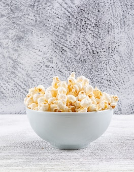 Side view of popcorn in bowl on white wooden table vertical