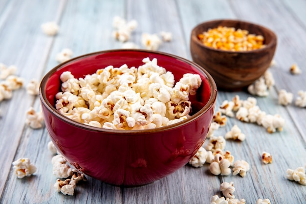 Side view of popcorn on a red bowl with popcorn isolated on grey wood