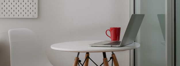 Side view of portable workspace with laptop, coffee mug and copy space