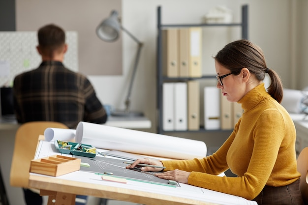 Side view portrait of adult female architect drawing blueprints while working at desk in office,