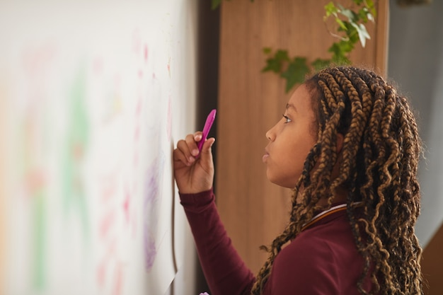 Side view portrait of african-american girl drawing on wall at home or in art class, copy space