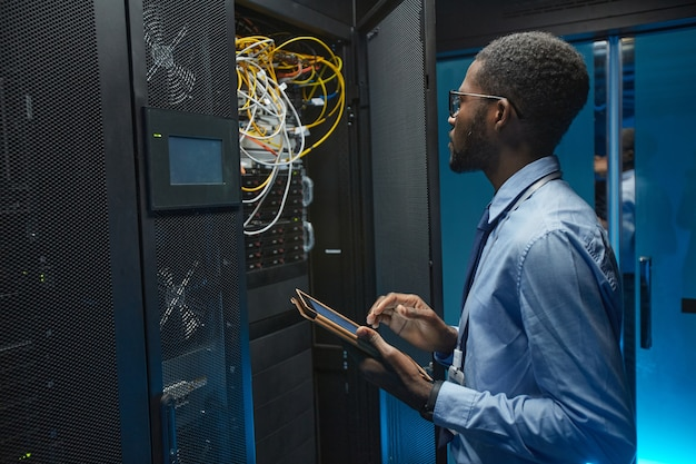 Side view portrait of african american man standing by server cabinet while working with supercomputer in data center and holding tablet, copy space