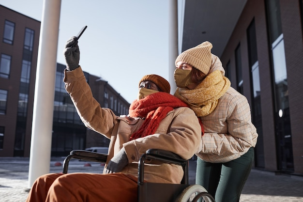 Side view portrait of african american man using wheelchair and wearing mask while taking selfie photo with young woman assisting in urban city, copy space
