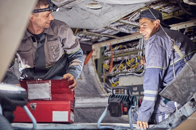Side view portrait of aircraft engineers working on undercarriage area with aviation equipments inside commercial airplane
