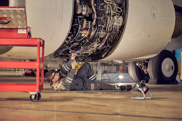 Side view portrait of airplane maintenance mechanic inspecting and tuning plane engine in a hangar